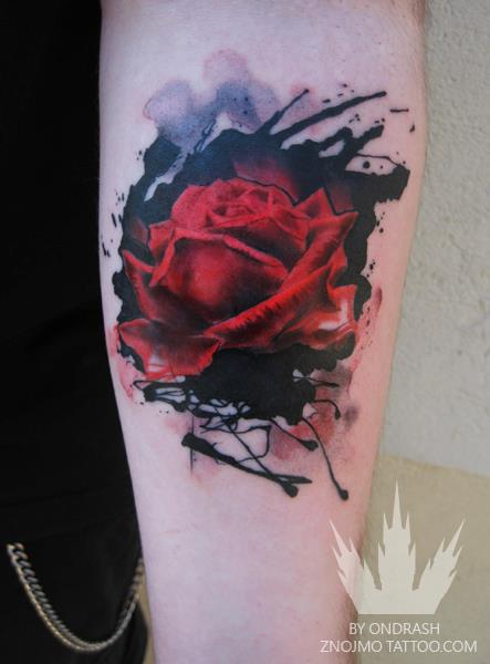 A beautiful red rose sits among ink splatters in this stunning watercolor flower tattoo by Ondrash