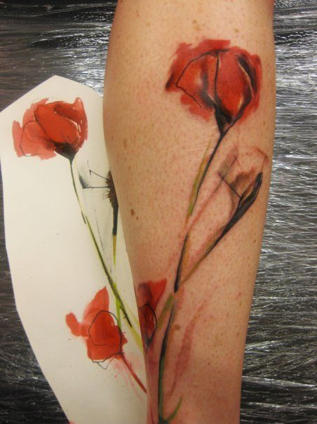 A painting of a watercolor poppy is transferred to skin by tattoo artist Ondrash
