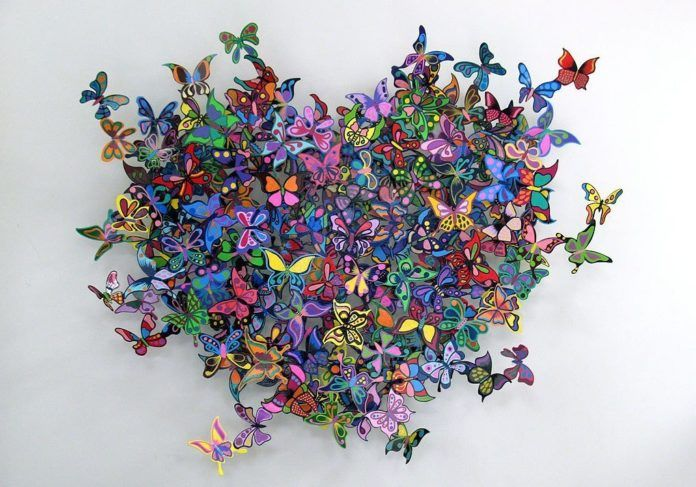A David Kracov metal art sculpture that creates a heart out of colorful and pretty butterflies