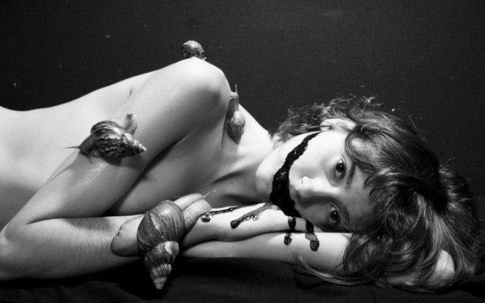 A Katerina Bodrunova surrealist photograph of a woman with snails crawling all over her body