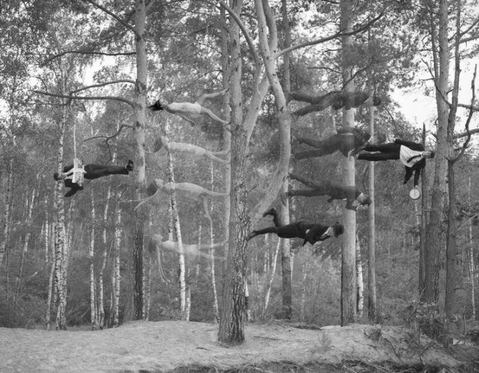 A Katerina Bodrunova surrealist photograph of people walking up and down trees