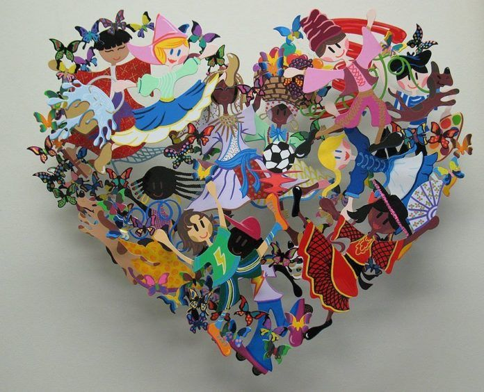 A colorful David Kracov sculpture that uses cut outs of children and butterflies to create a heart