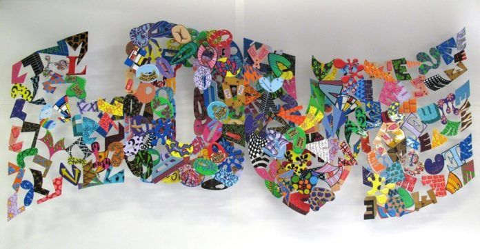 A colorfully painted metal sculpture of the word love by artist David Kracov