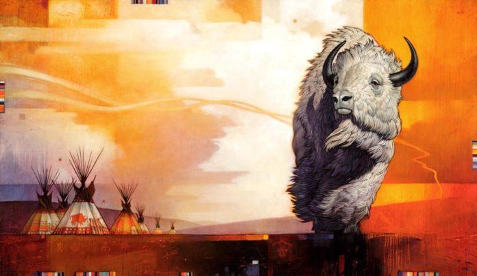 A native American inspired painting of a bison totem animal standing near teepees at dawn by Craig Kosak