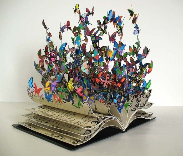 The Book of Life, a colorful metal art sculpture by David Kracov that depicts a book dissolving into butterflies