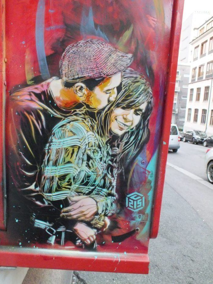 A cute and romantic graffiti art piece by French graffiti artist C215 of a young couple kissing and cuddling