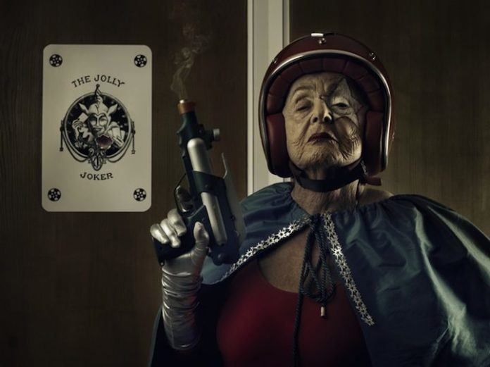 A funny photo by Sacha Goldberger of his grandmother in a superhero outfit and make-up posing like one tough old lady