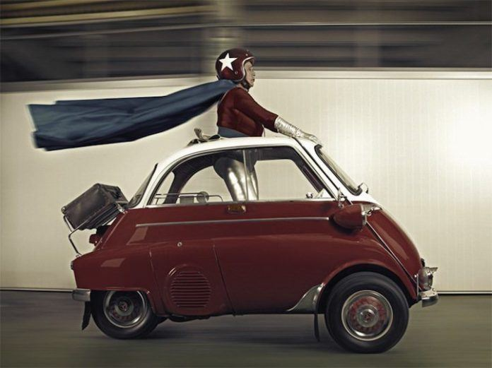 A funny photo by Sacha Goldberger of his grandmother in a superhero outfit driving a car standing up with her cape flying