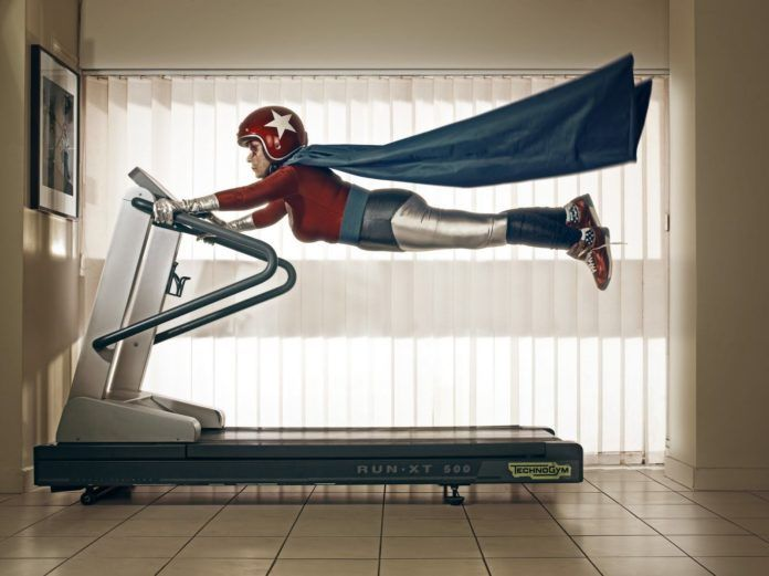 A funny photo by Sacha Goldberger of his grandmother in a superhero outfit flying on a treadmill