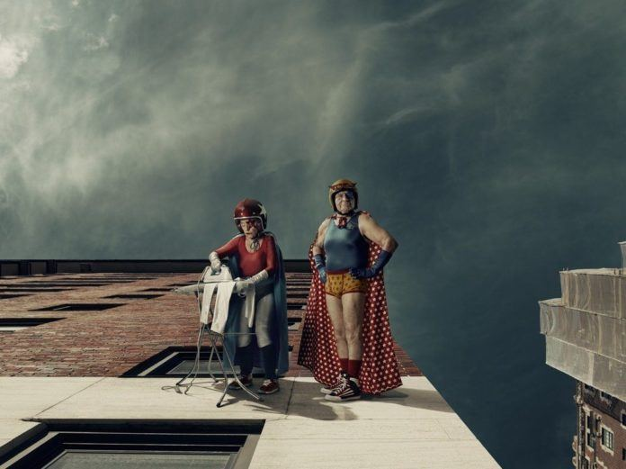 A funny photo by Sacha Goldberger of his grandmother in a superhero outfit ironing on the side of a building