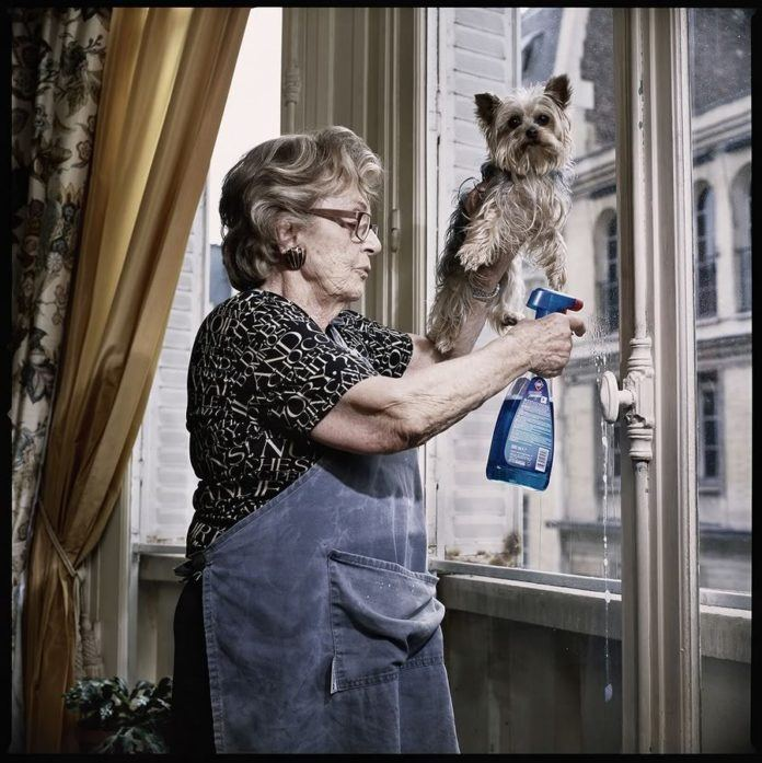 A funny photo by Sacha Goldberger of his grandmother washing a window with a little dog