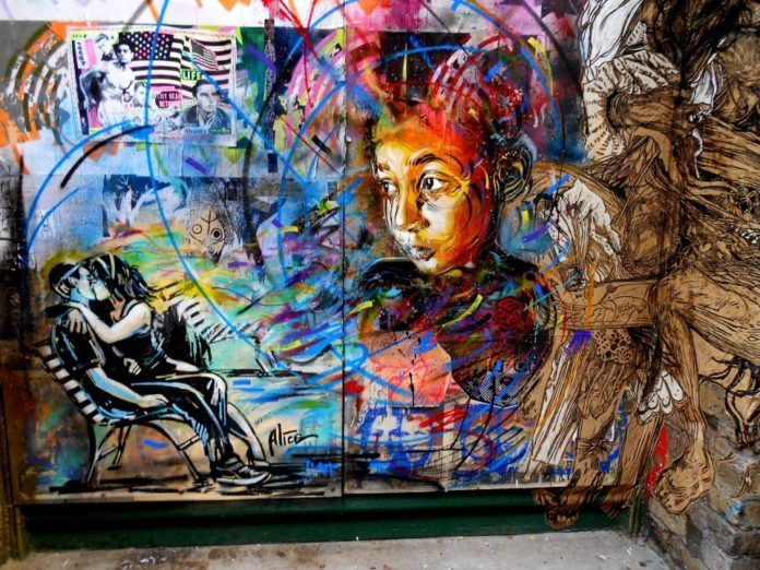 A graffiti art mural by French urban street artist C215 of a girls face and a couple kissing on a park bench