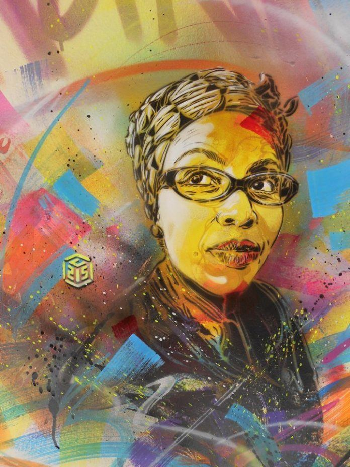 A stencil and spray paint graffiti art work of an African woman with glasses by urban street artist C215