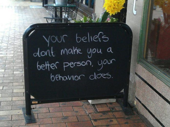 An photo of an inspirational quote on a chalkboard about behavior and beliefs