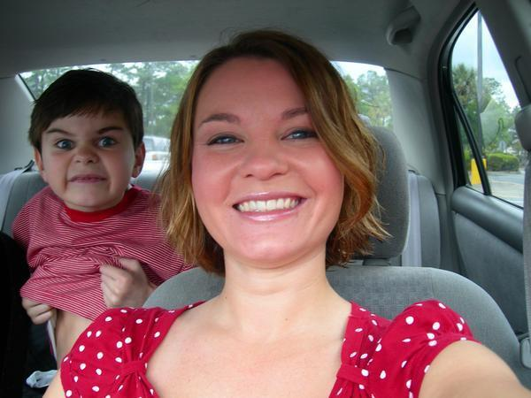 Evil kid photobombs his mom from the back seat of the car