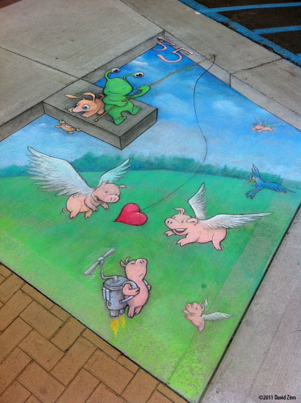 A cartoon surrealist chalk drawing on a pavement by David Zinn of an alien fishing for flying pigs