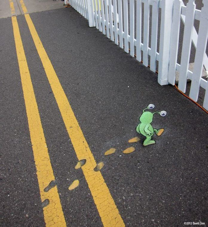A cute graffiti chalk drawing by David Zinn of a little green alien walking through wet painted street lines