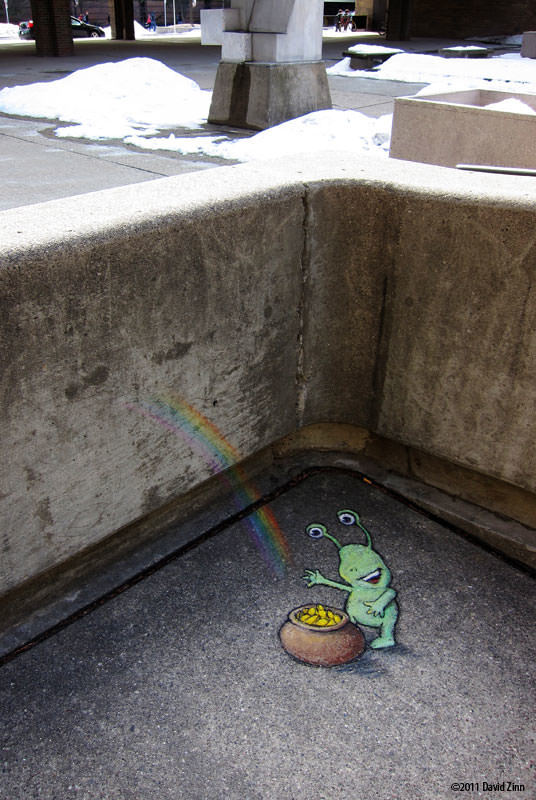 A cute little alien finds a pot of gold in this chalk graffiti art drawing by David Zinn