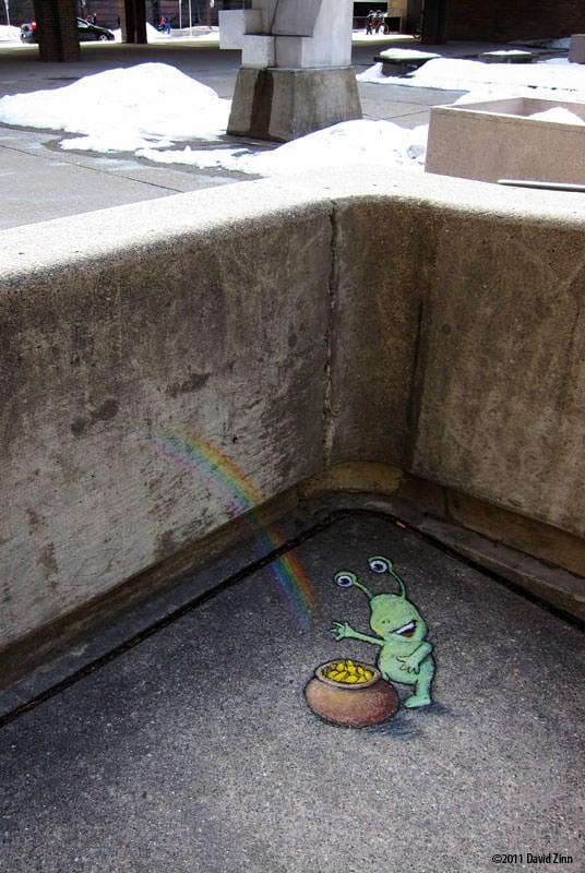 A cute little alien finds a pot of gold in this chalk graffiti art drawing by David Zinn