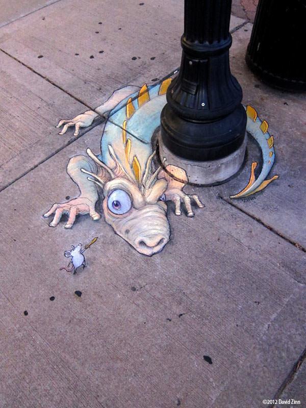 A funny graffiti chalk drawing by David Zinn of a brave mouse waving a sword at a beastly dragon