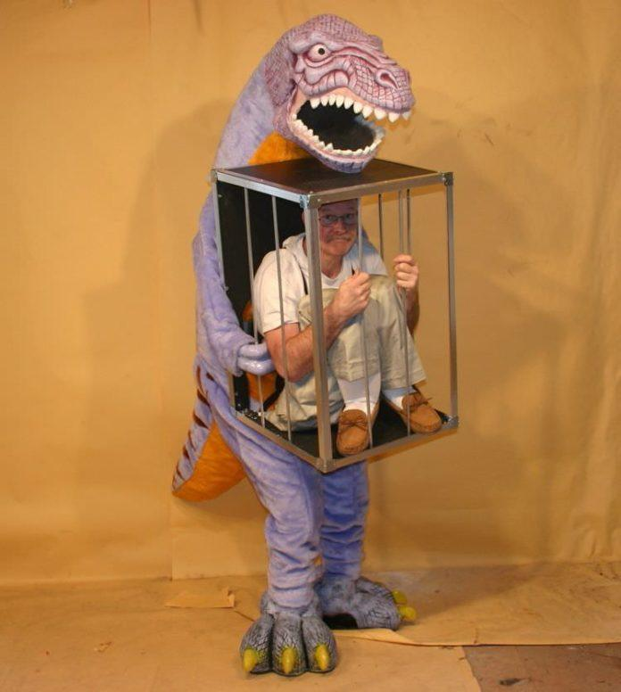 A funny halloween costume that looks like a dinsoaur holding a guy in a cage