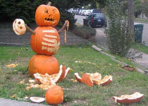 A funny halloween display of a pumpkin man slasher that has murdered another pumpkin