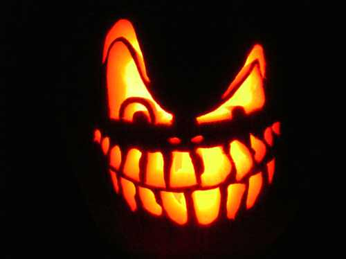 A funny halloween picture of a pumpkin carved with an evil grin