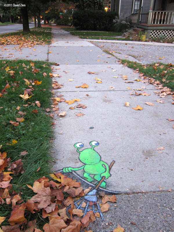 A funny sidewalk chalk drawing by David Zinn of an alien sweeping leaves under the paving stones