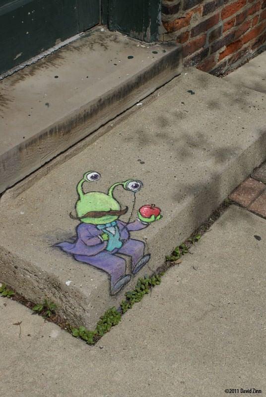 An aristocratic alien inspects an apple in this graffiti art chalk drawing by David Zinn