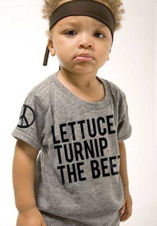 A cute picture of a kid wearing a shirt that says lettuce, turnip, the beet