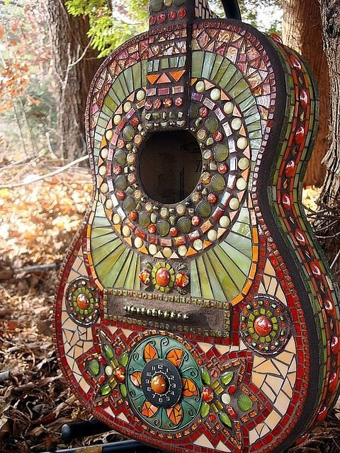 An acoustic guitar decorated with mosaic tiles for a hippy hipster style instrument