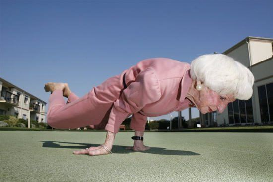 An inspirational picture of an old lady doing a handstand, proving that you're never too old to be fit