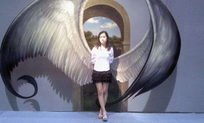 A pretty girl gets angel wings in an interactive optical illusion at the Trick Art Musuem in Korea