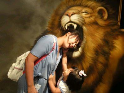A woman puts her head in the mouth of a lion at the Trick Art Museum in Korea