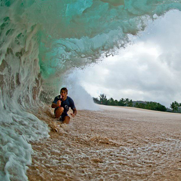 An inspirational picture of a brave guy taking a photo under a monster wave