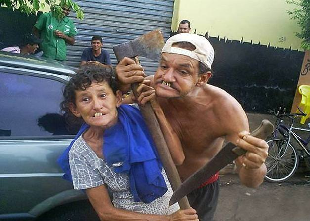A man and a woman pull funny faces while holding an axe and a machete