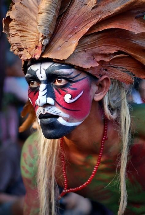 Fantastic inspirational photograph of an Indonesian warrior with head dress and face paint