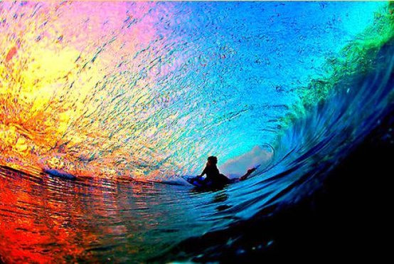 A surfer is surrounded by a rainbow of light and water in this inspirational sports photo