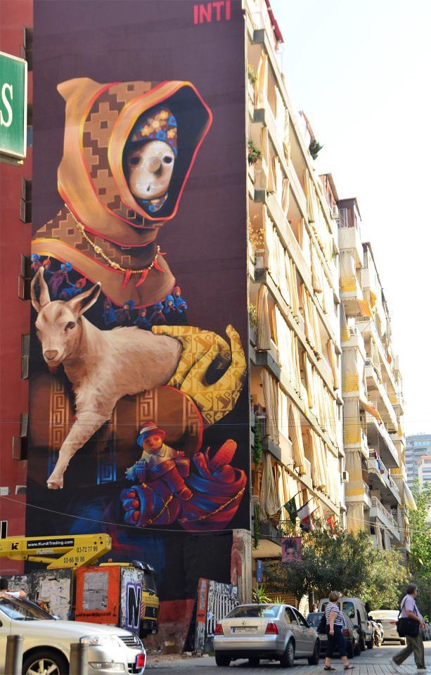 An enormous pop surrealist street art work of a sheperd with a lamb by graffiti artist Inti