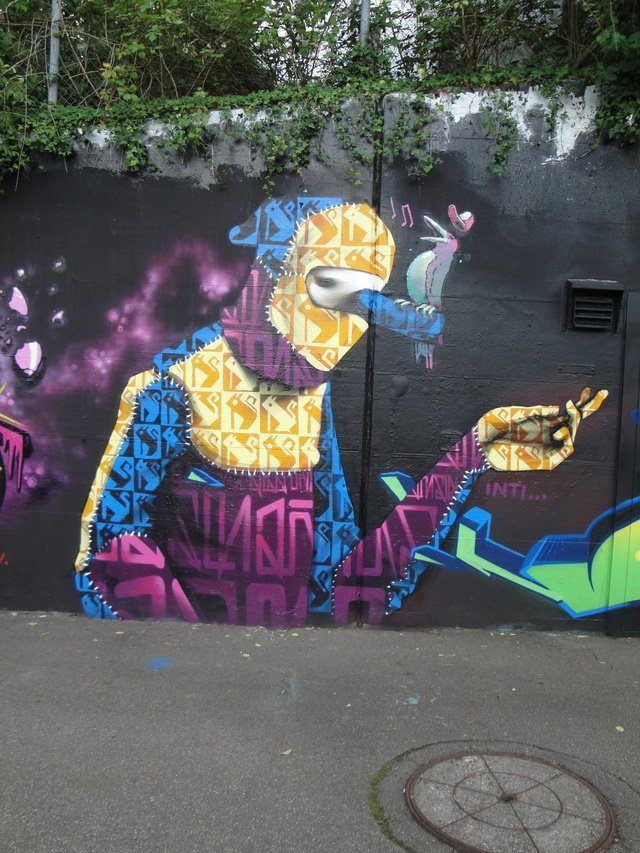 An original character appears in this street art painting by graffiti artist inti