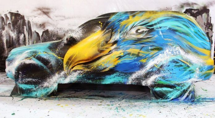 Chinese graffiti artist paints an eagle on a subaru, combining street art and traditional art styles