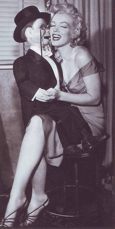 Marilyn Monroe receives a kiss from a ventriloquist puppet in this cute photograph