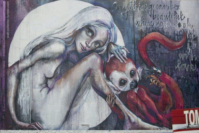 A graffiti painting by German artist Herakut of a nude girl in the moon with a pet monkey and a saying about beauty and love