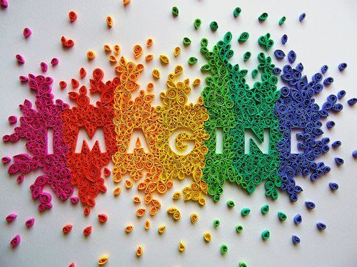 A paper art design that uses colorful, curled paper to form the word imagine