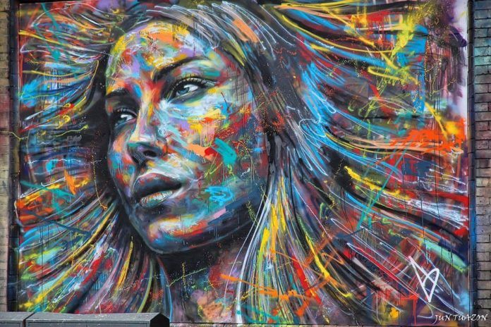A colorful spray paint portrait of a beautiful girl by London graffiti artist David Walker