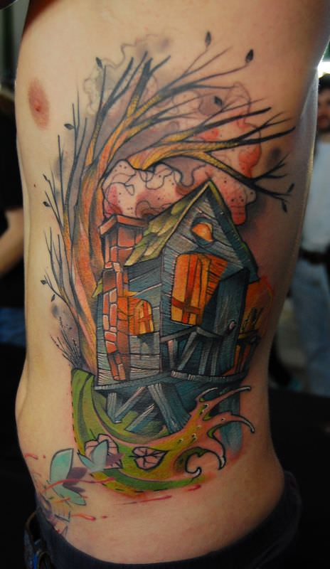 A cozy wood cabin stands in a windswept swamp in this artistic tattoo by Jukan