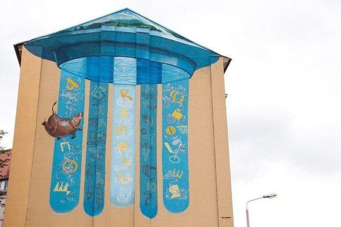Graffiti art team 140 Ideas paints a cow falling from a UFO in this creative street art mural