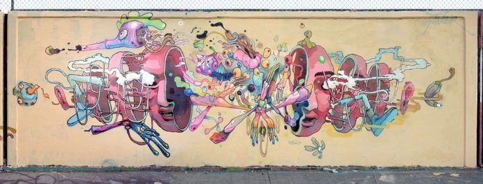 Mexican graffiti artist Dhear One designs a street ar mural of a human head falling to pieces and revealing a strange biology