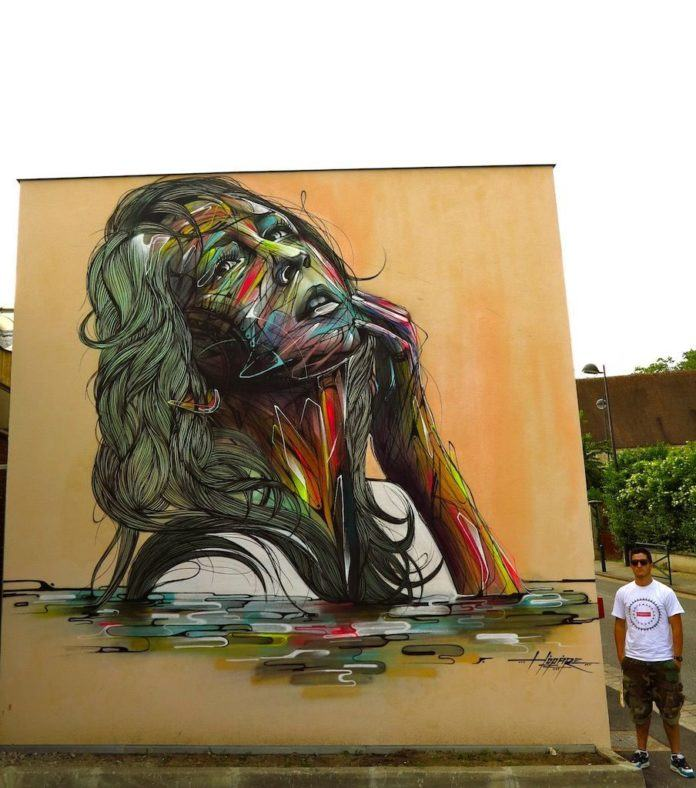 A beautiful woman poses eternally in this large street art mural by french graffiti artist Hopare