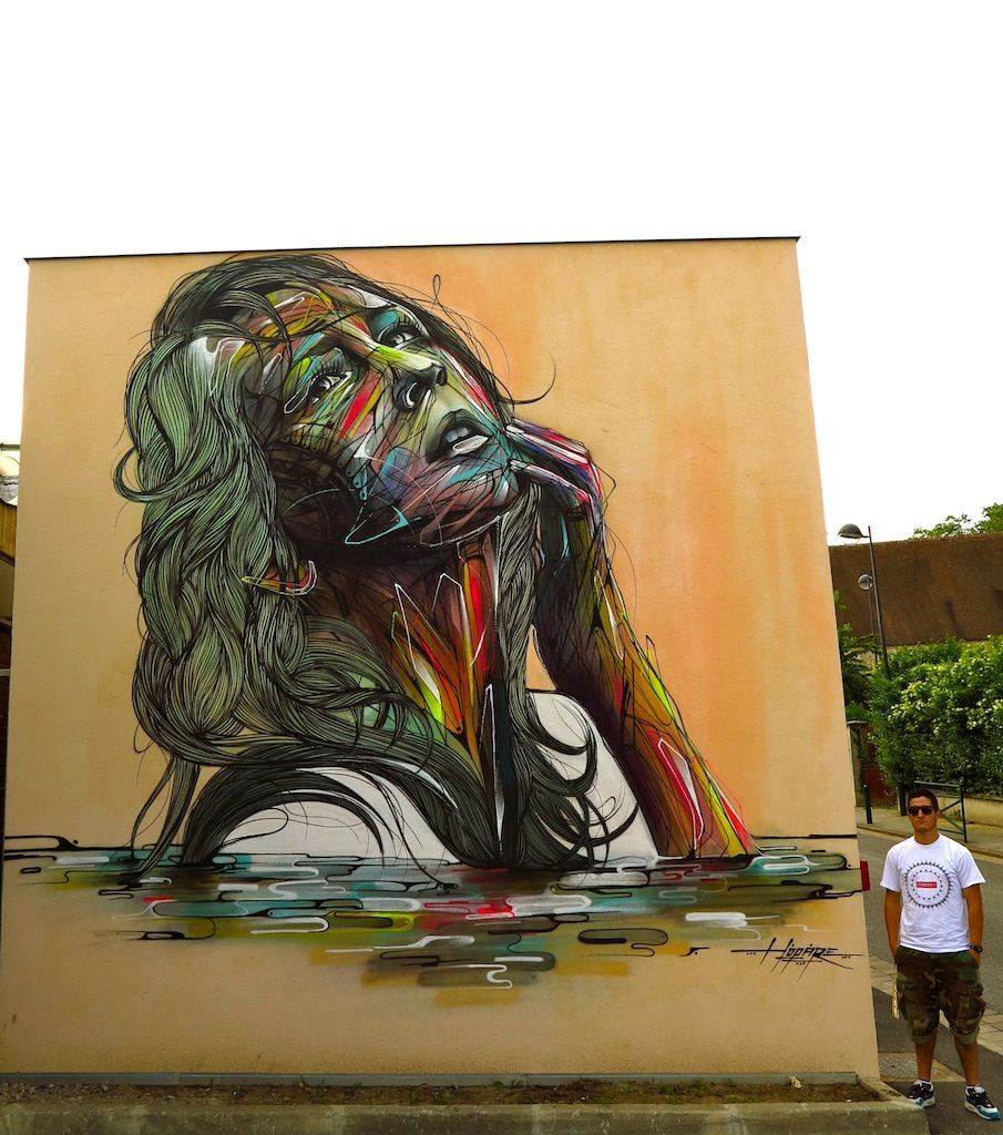 A beautiful woman poses eternally in this large street art for Mural graffiti